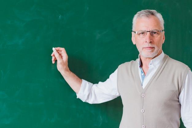 Senior male teacher writing on green chalkboard Free Photo