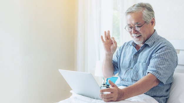 Senior male using a laptop computer facetime call to relatives Premium Photo