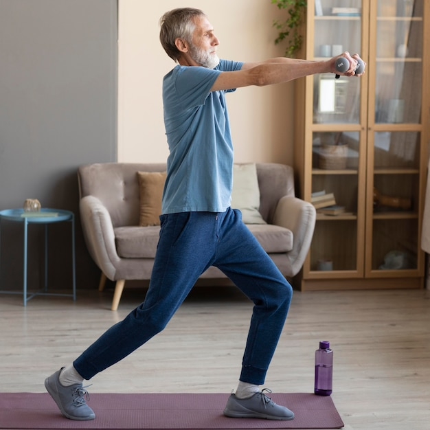 Senior male working out at home Free Photo