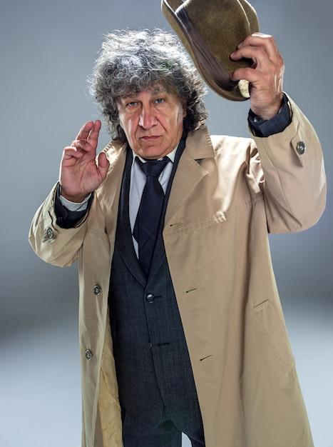 L'uomo senior come detective o capo della mafia su sfondo grigio studio Foto Gratuite
