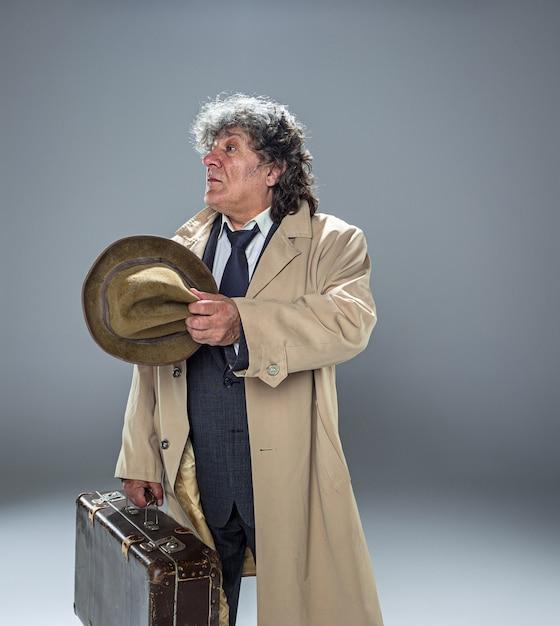 L'uomo anziano come detective o capo della mafia nello spazio grigio dello studio Foto Gratuite