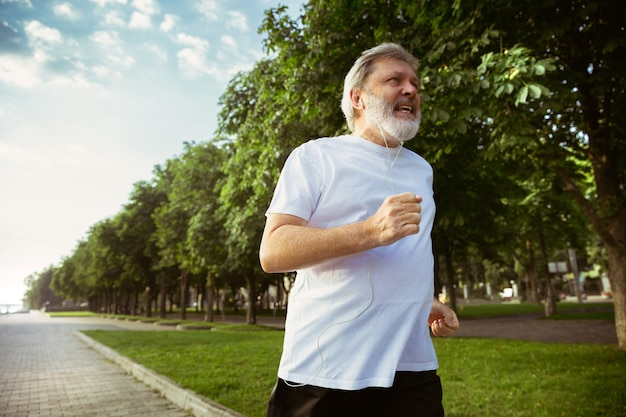 Senior man as runner with armband or fitness tracker at the city's street. caucasian male model practicing jogging and cardio trainings in summer's morning. healthy lifestyle, sport, activity concept. Free Photo