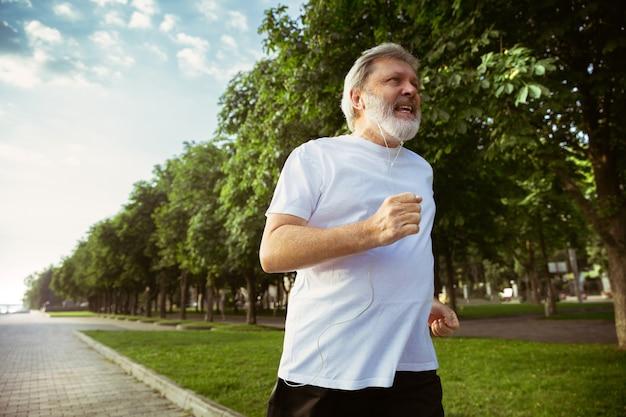 街の通りで腕章またはフィットネストラッカーを持つランナーとしての年配の男性。夏の朝にジョギングとカーディオトレーニングを練習している白人男性モデル。健康的なライフスタイル、スポーツ、活動の概念。 無料写真