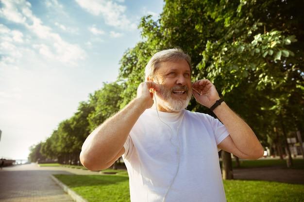 街の通りでフィットネストラッカーを持つランナーとしての年配の男性。夏の朝にジョギングや有酸素運動をしながらガジェットを使用する白人男性モデル。健康的なライフスタイル、スポーツ、活動の概念。 無料写真