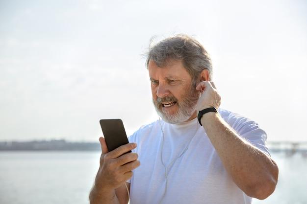 川沿いでフィットネストラッカーを持つランナーとしての年配の男性。 無料写真