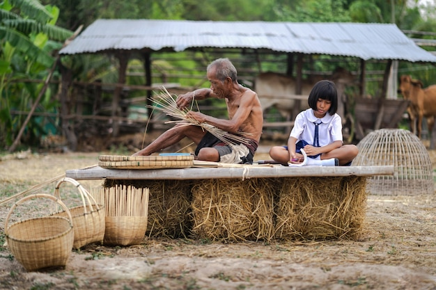 Senior man and bamboo craft with student girl, lifestyle of the locals, thailand Premium Photo