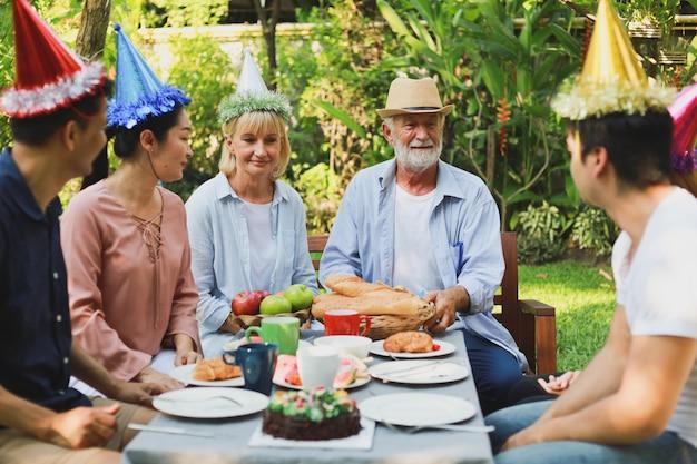 Senior man birthday party in garden Premium Photo