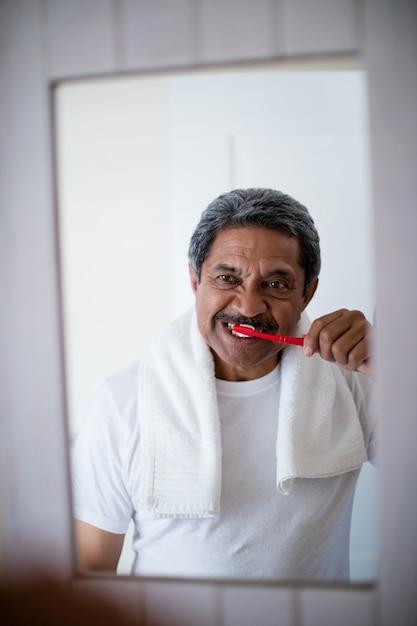 年配の男性がバスルームで歯を磨く Premium写真
