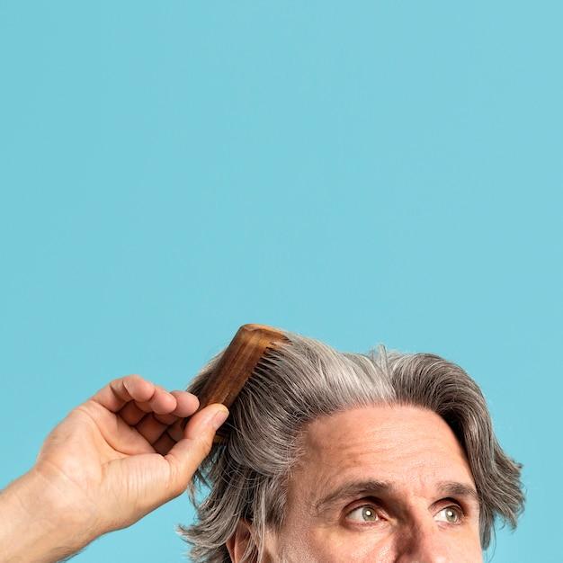 コピースペースで彼の髪をとかすシニア男性 無料写真