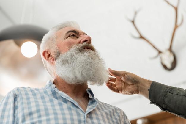 Senior man consulting on beard trimming in salon Free Photo