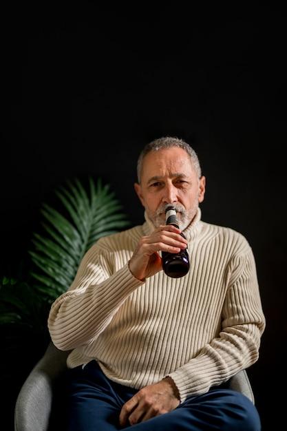 Senior man drinking cold beer Free Photo
