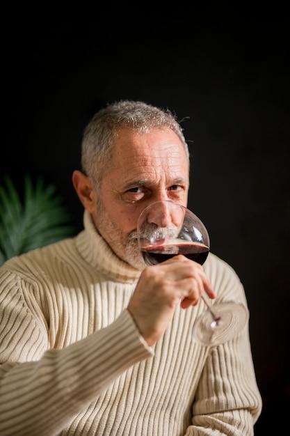 Senior man drinking red wine Free Photo