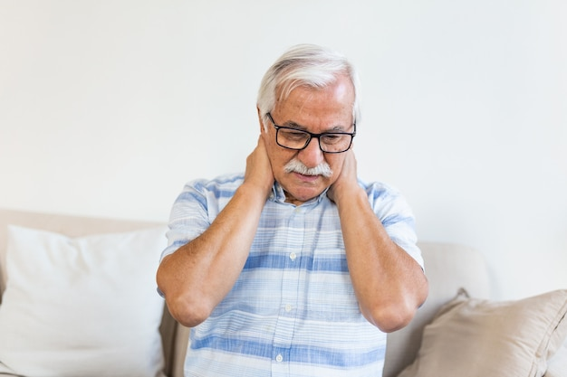 Senior man feeling exhausted and suffering from neck pain Premium Photo