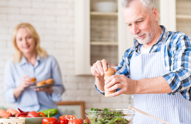 Senior man grinding pepper to salad and her wife enjoying the muffins at background in the kitchen Free Photo