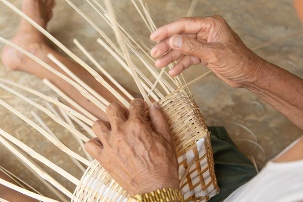 Senior man hands manually weaving bamboo. Premium Photo