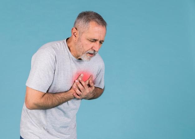Старший мужчина, имеющий боль в груди на синем фоне Premium Фотографии