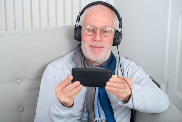Senior man in headphones listening to music at home Premium Photo