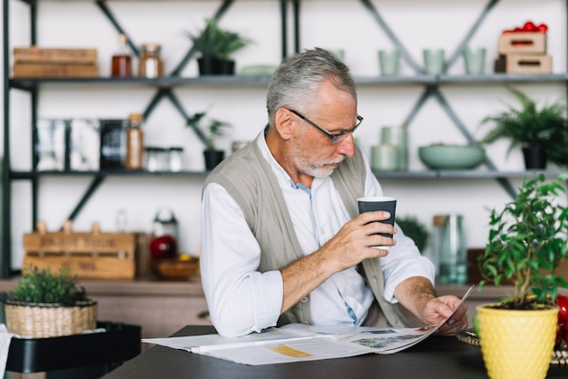 Senior man holding coffee cup in hand reading newspaper Free Photo