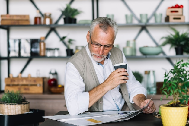 Senior man holding cup of coffee reading newspaper at home Free Photo