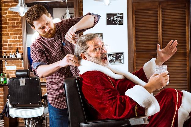 Старший мужчина в костюме санта-клауса бреет своего личного мастера в парикмахерской перед рождеством Бесплатные Фотографии