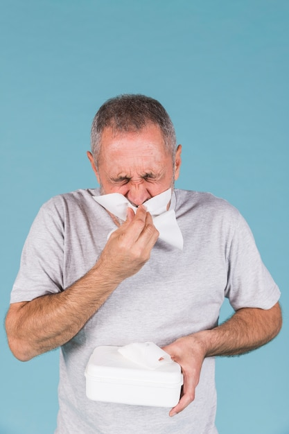 Senior man infected with cold and flu blowing his nose in tissue paper Free Photo