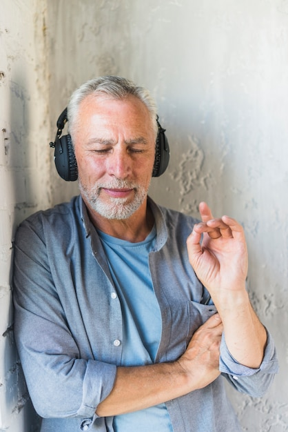 Senior man leaning on wall listening music on headphone Photo | Free