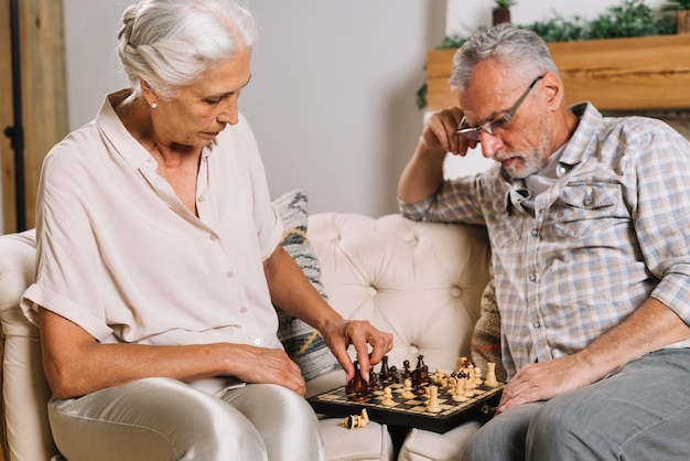 Senior man looking at her wife playing chess Free Photo