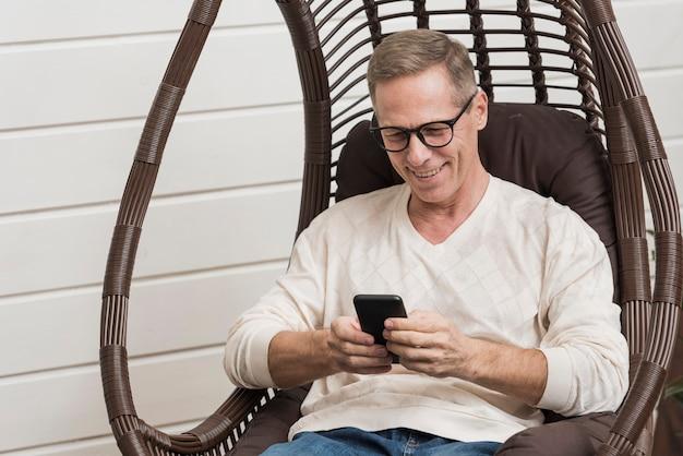 Senior man looking on his phone Free Photo