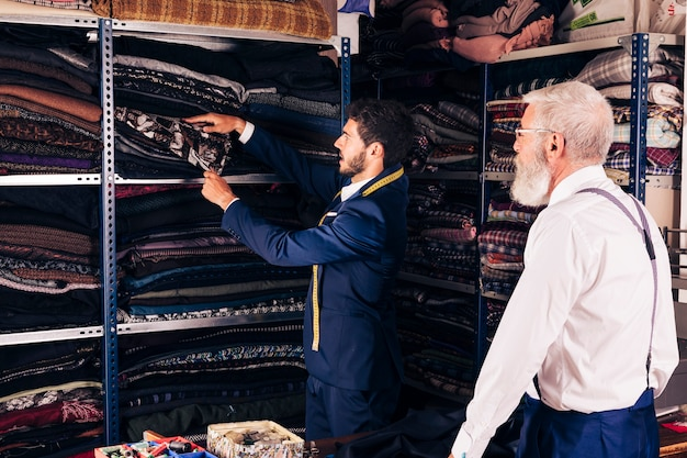 Senior man looking at male tailor taking fabric from shelf in the workshop Free Photo