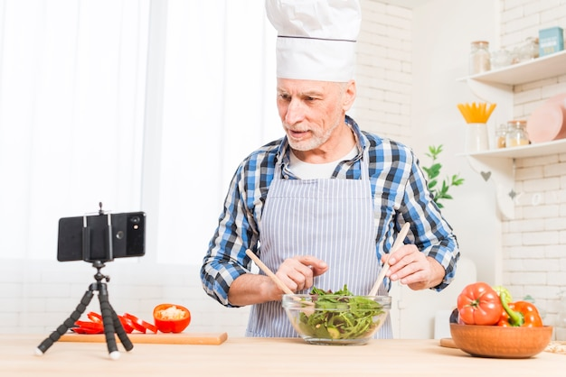 Senior man looking at mobile phone while preparing the salad in the kitchen Free Photo