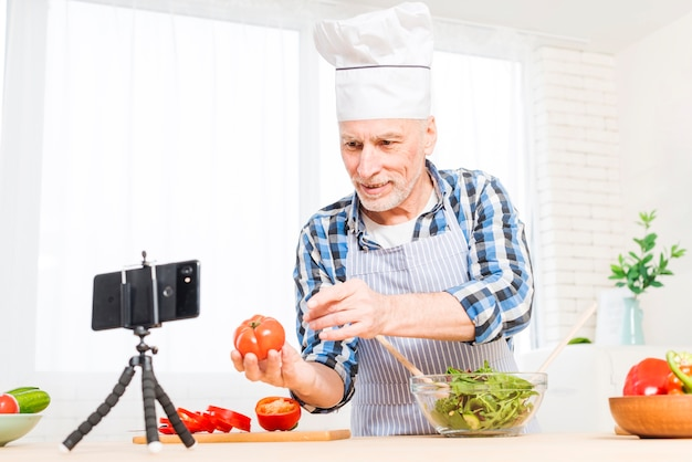 Senior man making video call on mobile phone showing heirloom tomato while preparing salad Free Photo