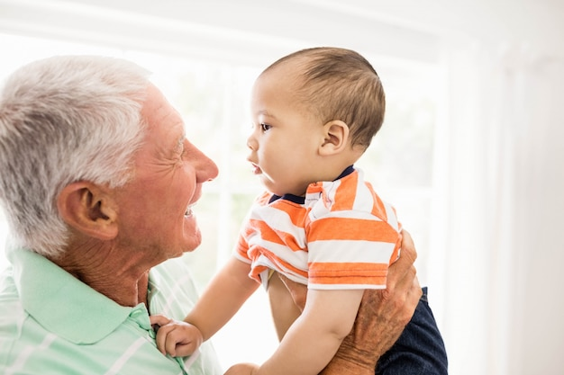 Senior man playing with his grandson at home Premium Photo