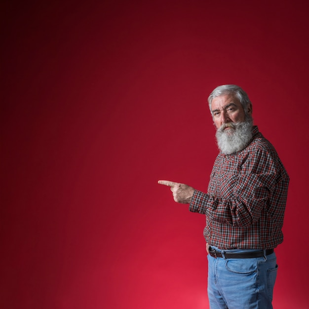 Senior man pointing his finger at something against red background Free Photo