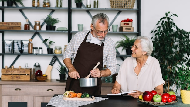 Senior man preparing food looking at book hold by senior woman Free Photo