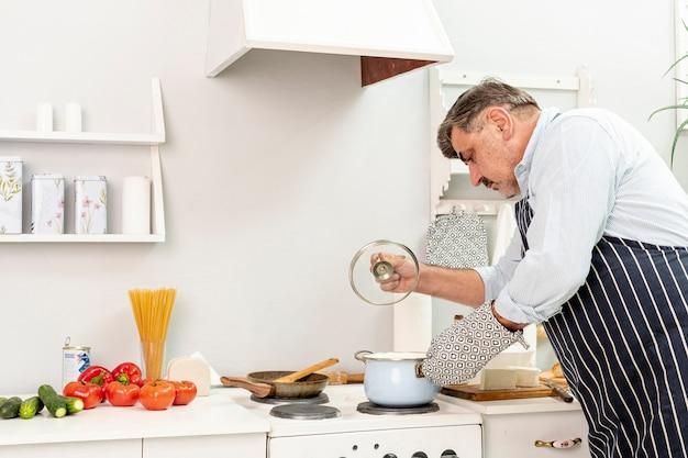 Senior man raising a cover pot Free Photo