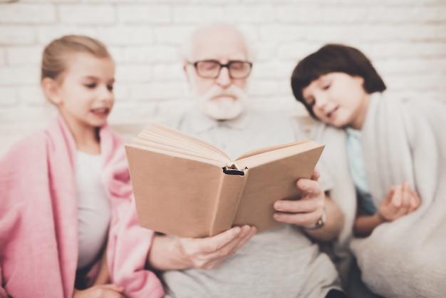 Senior man reading story book for two grandkids Premium Photo