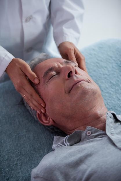 Senior man receiving head massage from physiotherapist Premium Photo