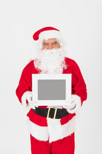 Senior man in santa claus costume holding empty frame Free Photo