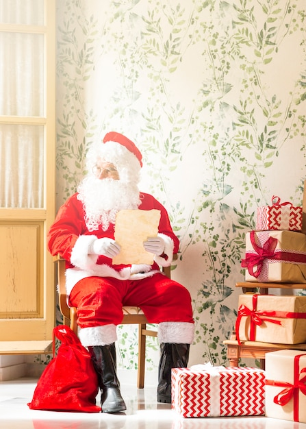 Senior man in santa claus costume sitting with wish list Free Photo