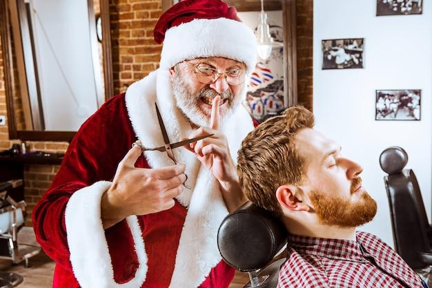 L'uomo anziano in costume di babbo natale lavora come maestro personale con le forbici al negozio di barbiere prima di natale Foto Gratuite