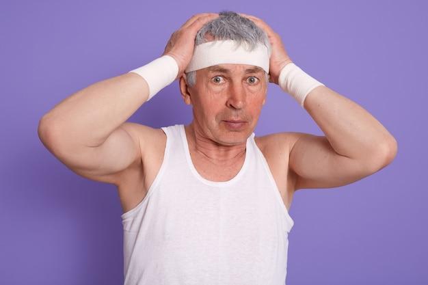 年配の男性が混乱で頭をかいて、白いノースリーブのtシャツを着て、彼の頭に触れて、ライラックの壁に分離されたポーズ 無料写真