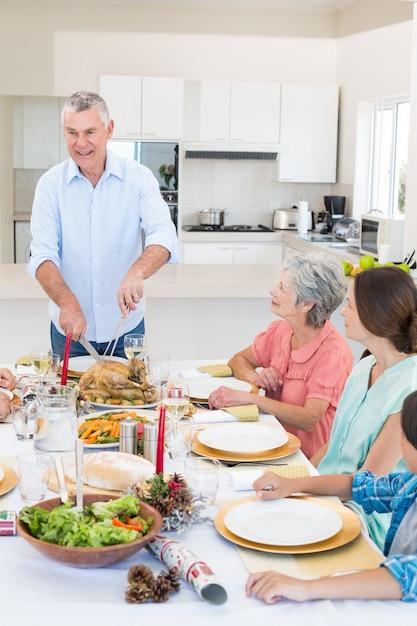 Senior man serving meal to family Premium Photo