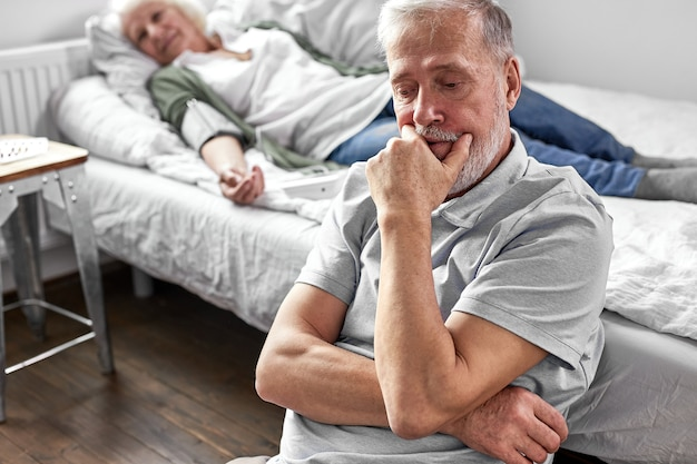 Старший мужчина сидит с больной больной женой, лежа на кровати, плохо себя чувствует, женщина на пороге смерти, мужчина очень за нее переживает Premium Фотографии