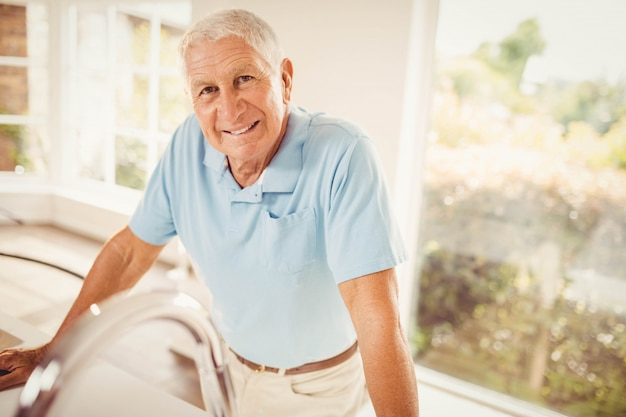 Senior man standing and looking at the camera in the kitchen Premium Photo
