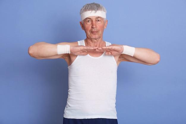 屋内で手を伸ばし、トレーニングやテニスをする前にウォーミングアップする年配の男性、白いtシャツ、ヘアバンド、リストバンドを身に着けている成熟した男性。 無料写真