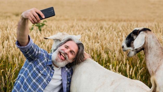 ヤギとslefieを取るシニア男性 無料写真