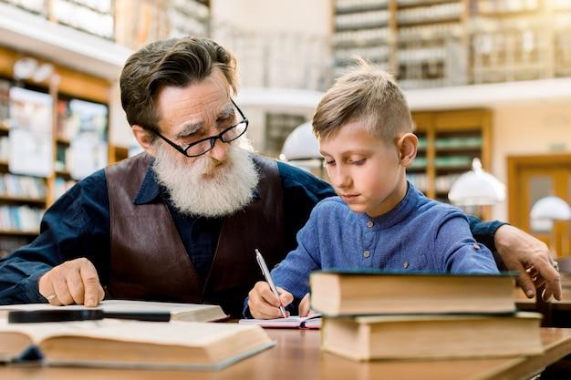 Старший мужчина учитель или дедушка обучения маленький мальчик, его внук, чтение книги в библиотеке, в то время как мальчик делает заметки в своей копии книги. образование, концепция школы Premium Фотографии