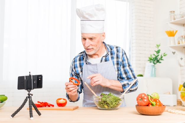 Senior man wearing white chef's hat making video call while cooking food in the kitchen Free Photo