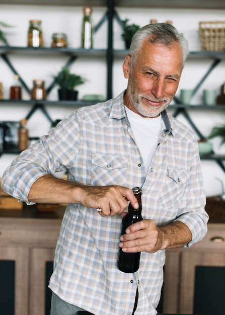 Senior man winking while opening the cap of beer bottle Free Photo