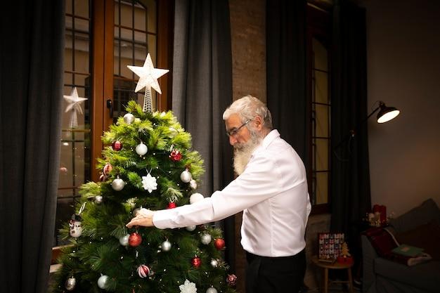 Senior man with beard next to christmas tree Free Photo